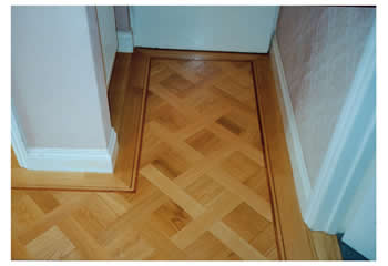 New parquet flooring, Cambridge. Oak parquet in basket weave pattern with large dot design and mahogany two-line border..