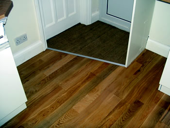 New wooden flooring, Finchley, London. Red oak engineered wood floor with door mat..